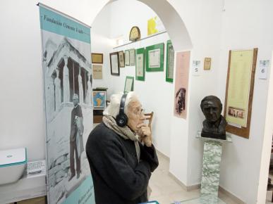 Abuela con auriculares escuchando una d las conferencias d Clemente y absorta recorre la muestra.